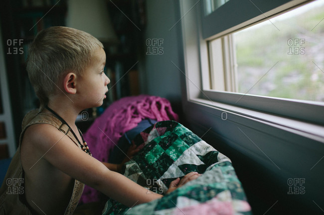 Boy looking out of an open window