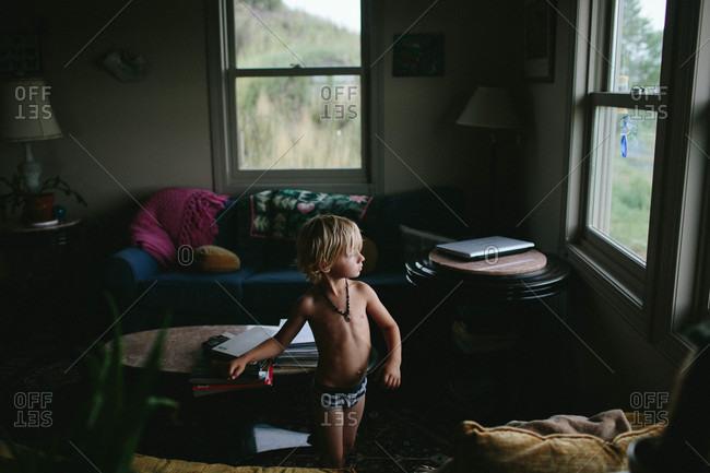 Boy in his underwear looking out window