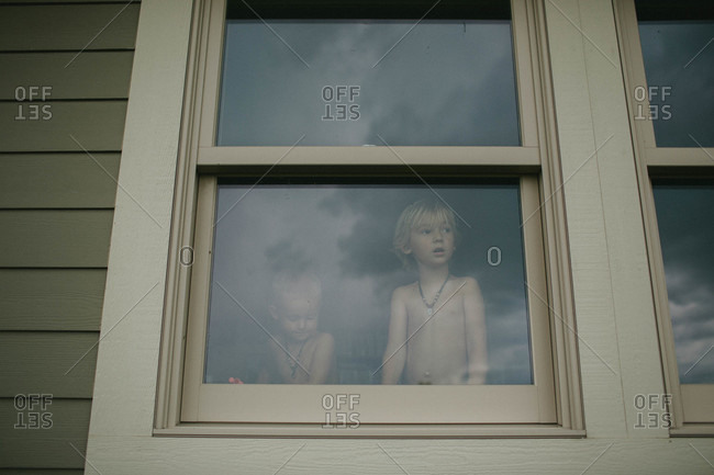 Boys looking out of window in a house