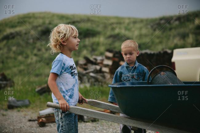 Boys playing with a wheelbarrow