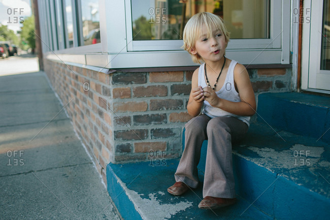 Boy sitting on steps in front of a store