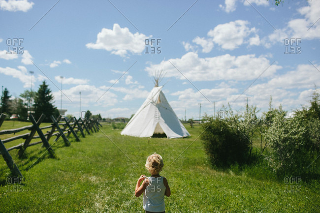 Boy walking toward a teepee