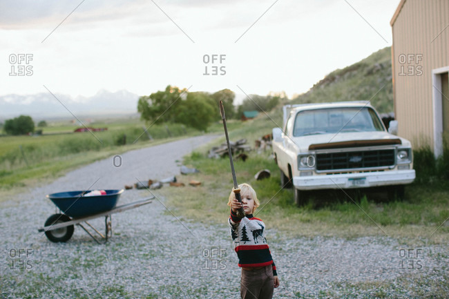Boy playing outdoors with a toy sword