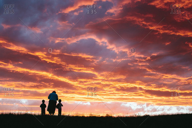 Grandmother and children in a field at sunset