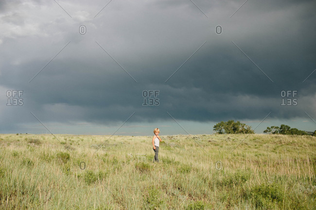 Boy standing in a field under storm clouds
