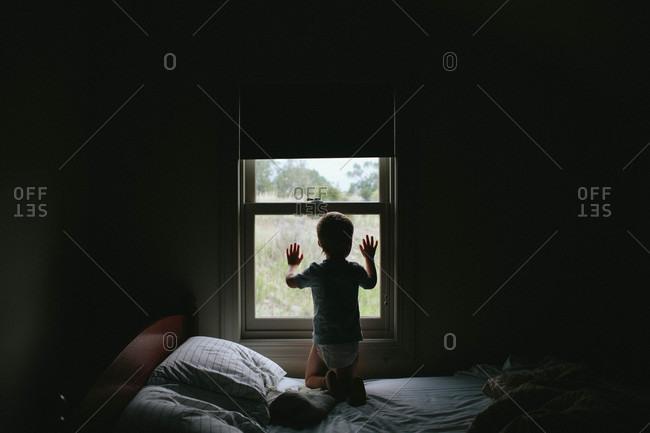 Little boy looking out bedroom window