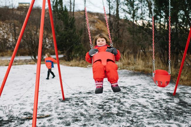 Girl on a park swing in winter