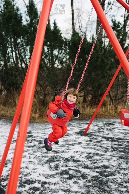 Girl on a park swingset in winter