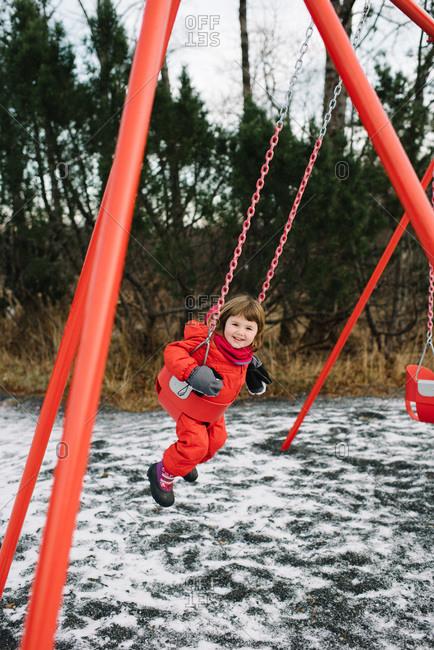 Girl on a park swingset in winter