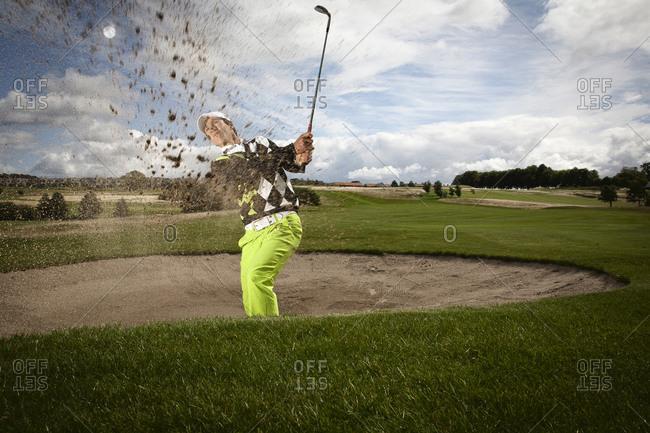 Copenhagen, Denmark - August 10, 2011:Thorbjørn Olesen swinging club to get ball out of a sand trap