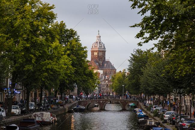 Amsterdam, Netherlands - September 7, 2012: View over Oudezijds Voorburgwal canal and Sint Nicolaaskerk, St. Nicholas church
