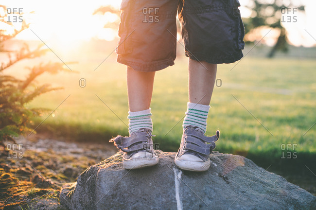 Boy with velcro shoes standing on a boulder