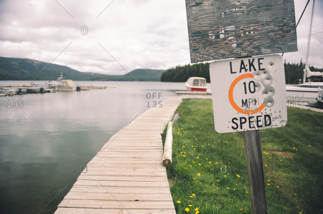 Lake speed limit sign with bullet holes