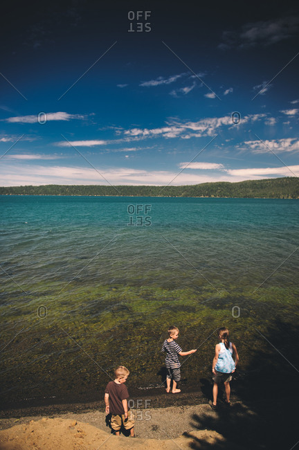 Children standing on a lake shore