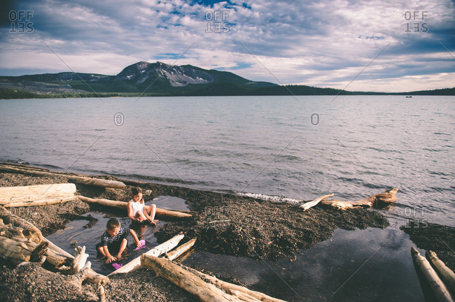 Children playing by a mountainside lake