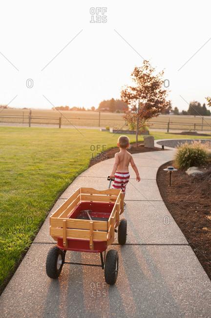 Boy pulling tractor on a sidewalk