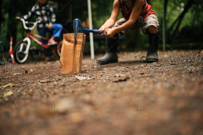 Boy using axe to split wood