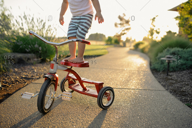 Boy standing on a tricycle seat