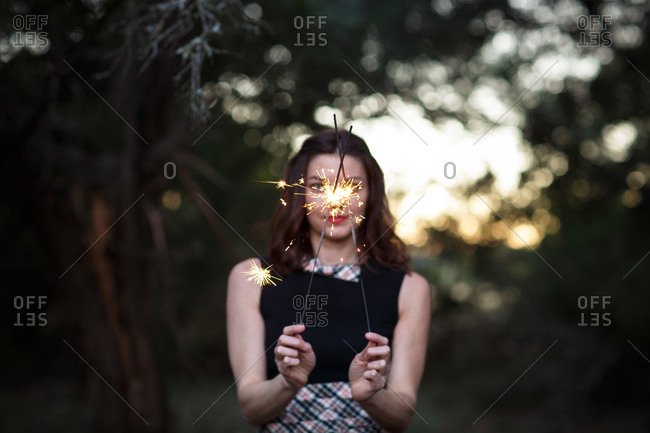 Woman in black dress holding sparklers in front of her face