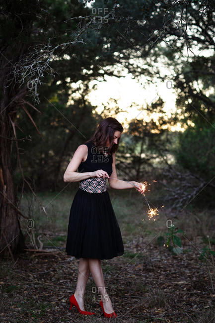 Woman in black dress and red heels holding sparklers