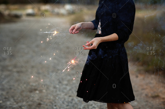Woman in black dress holding sparklers