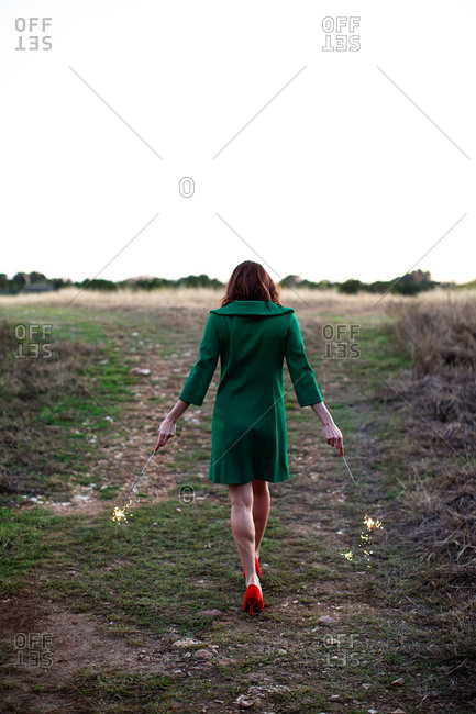 Woman in green coat and red heels holding sparklers