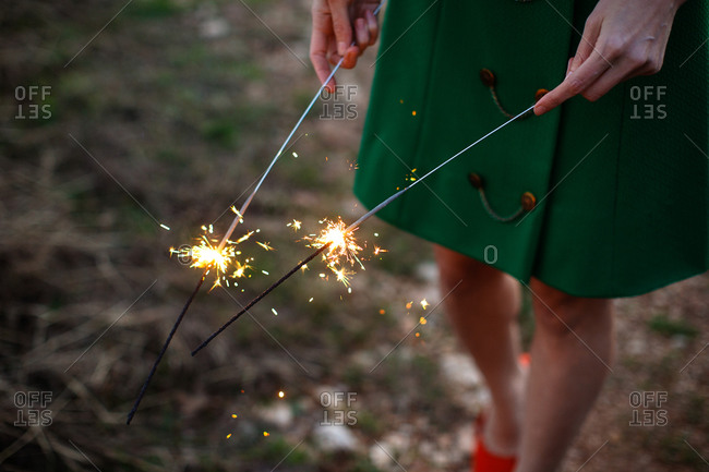 Woman in green coat holding sparklers