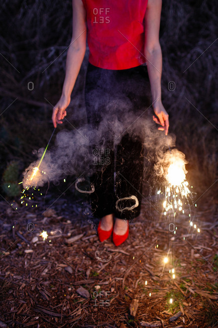 Woman in red shirt and heels holding sparklers