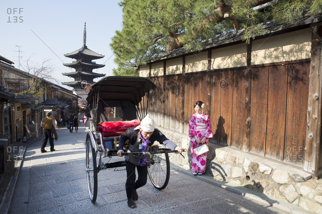 Kyoto, Japan - November 29, 2015: Man pulling rickshaw in front of the Kiyomizu-dera temple