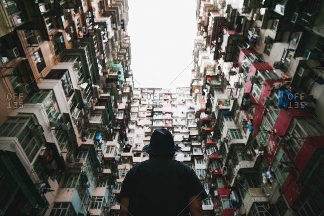 Man looking up at multiple apartments from an alley below