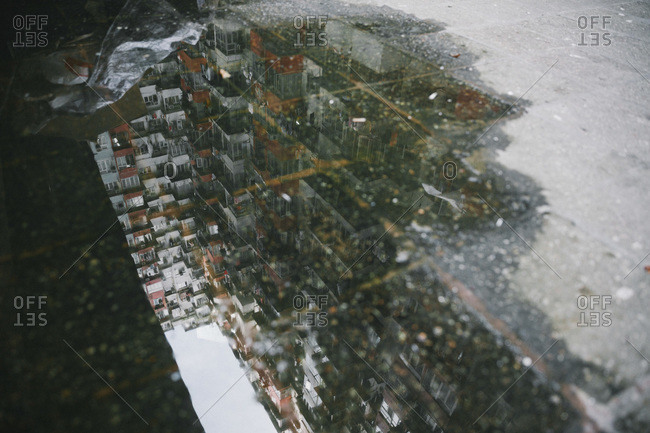Reflection of apartments and balconies in a puddle