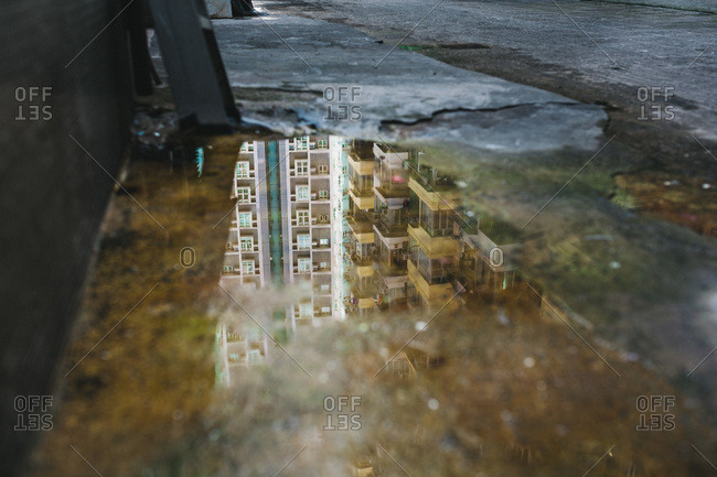 Reflection in a puddle of apartments and balconies