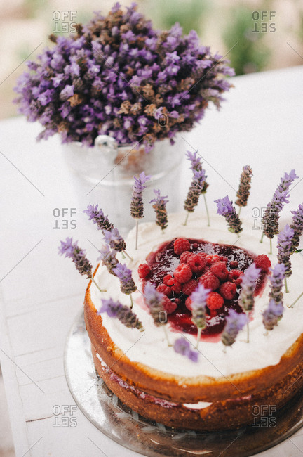 Cake topped with raspberries and purple flowers