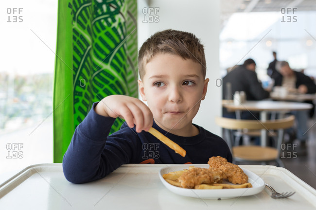 Boy eating French fries at a cafe