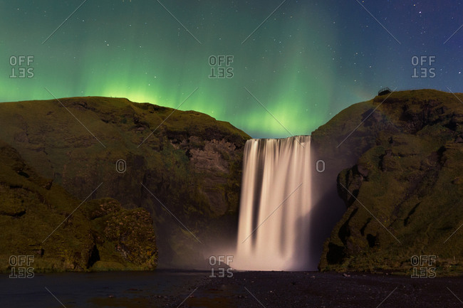 The aurora borealis dances over the giant waterfall, Skogafoss