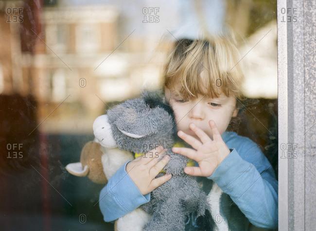 Little boy standing at a window holding stuffed animals