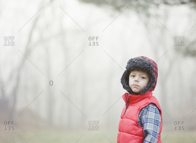 Little boy standing in a misty field