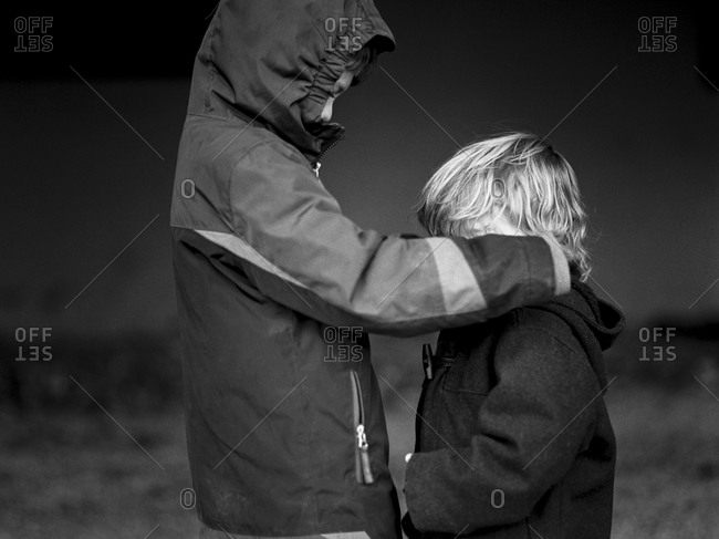 Boy adjusting his younger brother's coat