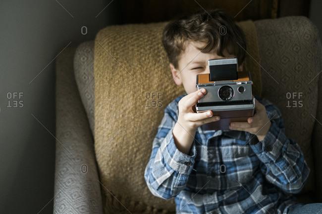 Little boy looking through a vintage camera