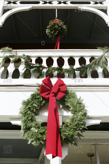 Mistletoe and Christmas wreath hanging from a porch railing