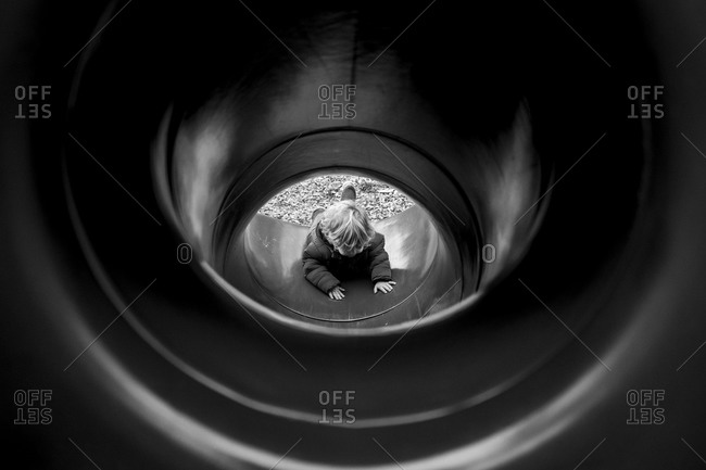 Little boy at the bottom of an enclosed slide