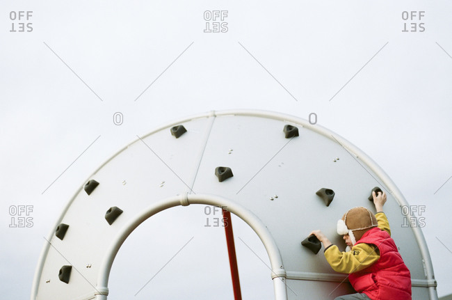 Boy on a circular climbing wall at a playground