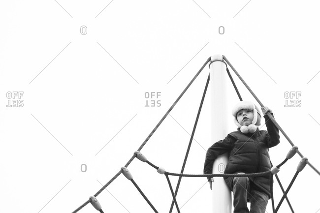 Boy standing on a climbing tower at a playground