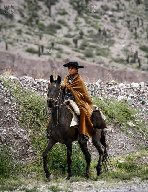 Quebrada de Humahuaca, Jujuy province, Argentina - January 6, 2012: Northern gaucho riding a horse near Purmamarca
