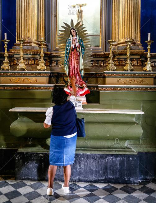 Salta, Argentina - January 5, 2012: Woman worshiping at San Francisco Church