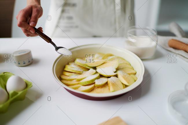 Female sprinkling sugar on apple slices