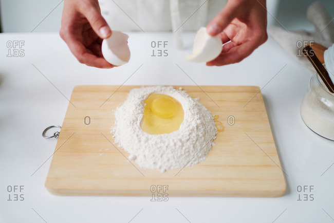 Female cracking an egg over cutting board with flour