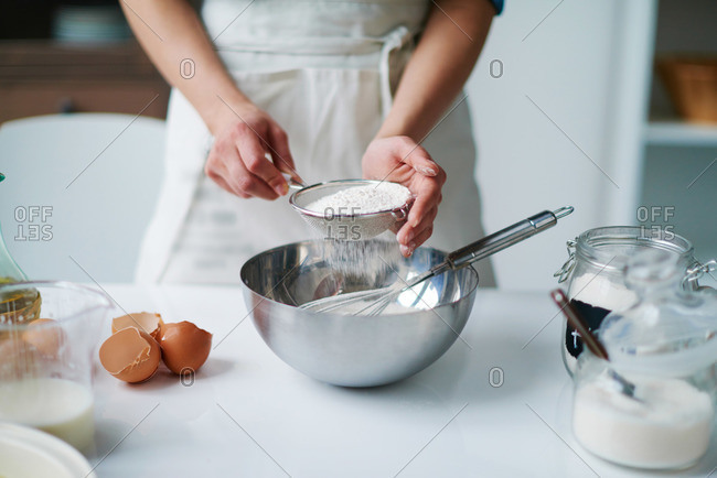 Woman sifting flour in a bowl