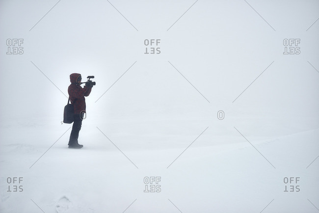 Lonely photographer shooting in winter field