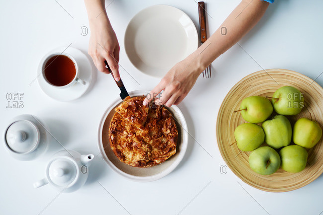 Female hand cutting a pie